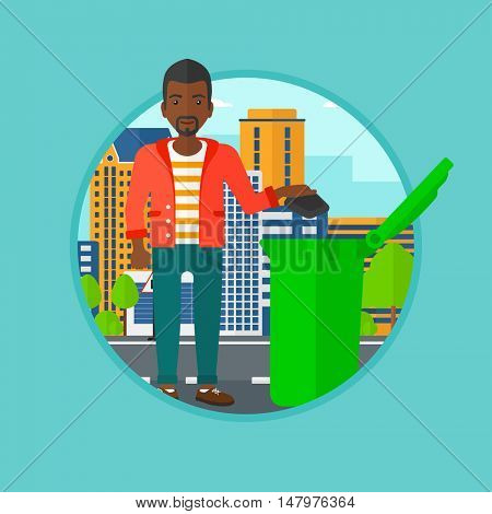 An african-american man throwing away a garbage in a green bin on a city background. Eco-friendly young man throwing trash. Vector flat design illustration in the circle isolated on background.