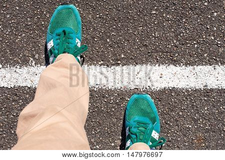 A pair of feet taking a step on an asphalt road across a white line. Concept of achievement.