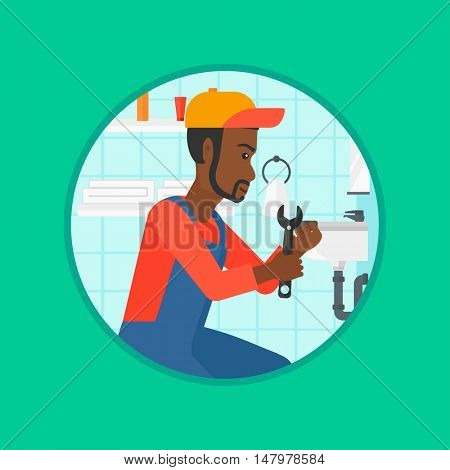 An african-american plumber sitting in a bathroom and repairing sink pipe. Plumber with wrench repairing a broken sink in bathroom. Vector flat design illustration in the circle isolated on background