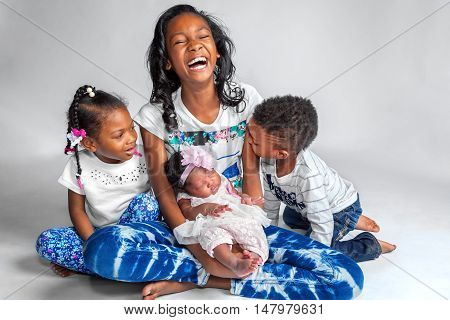Four African American siblings sit on a white background for a portrait. A laughing tween holds her newborn baby sister while her preschool age siblings sit at her sides.