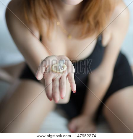 Woman showing a condoms on bed Focus on the condom in the foreground