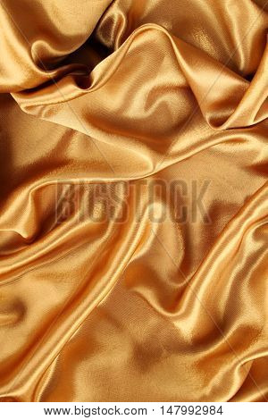 Background of bright shiny gold silk. Textured