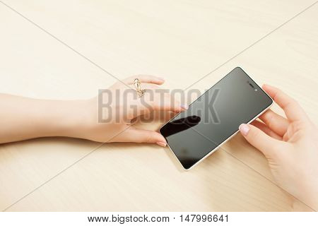 Female hands holding smartphone, customer pov, mockup. Woman using new phone with blank screen, wooden background, void. Free space for advertisement
