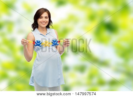 pregnancy, motherhood, people and expectation concept - happy pregnant woman holding rattle toy over green natural background