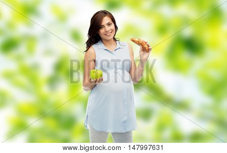 pregnancy, healthy eating, junk food and people concept - happy pregnant woman choosing between green apple and croissant over green natural background