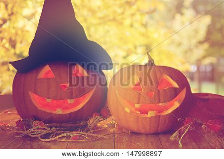 holidays, halloween and decoration concept - close up of pumpkins on wooden table over natural background