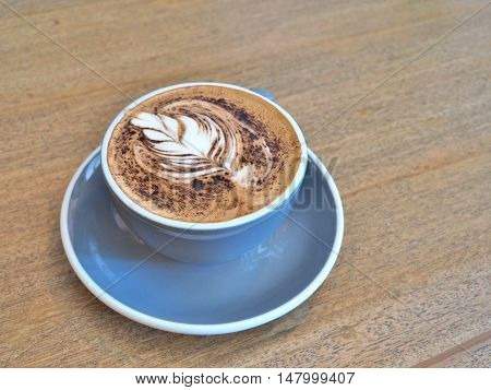 A cup of coffee with Rosetta pattern on wooden background.