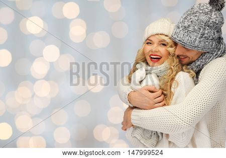 people, christmas, holidays and new year concept - happy family couple in winter clothes hugging over lights background