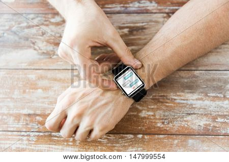 business, modern technology, social network, communication and people concept - close up of male hands setting smart watch with messenger on screen on wooden table