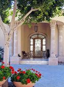 photo of frony door at home with nice setting of plants and trees to greet the guests poster