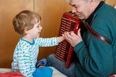Happy blond little kid boy and his grandfather playing together with accordion. Senior man teaching his grandson, cute toddler to play with music instrument at home. poster