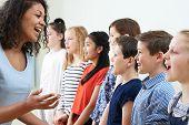 Children In School Choir Being Encouraged By Teacher poster