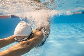 Emotional close-up photo of woman who swims underwater in the swimming pool outdoors. She wears dark swimsuit, white swim cap and swim glasses. Sunlight falls from above. Splashes are around her body. poster