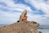 A pretty blonde in a one piece swimsuit relaxing on a boulder att he beach looking at the sea poster