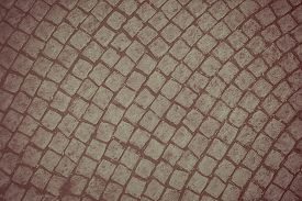 Background of old cobblestone pavement. Photo in brown tones.