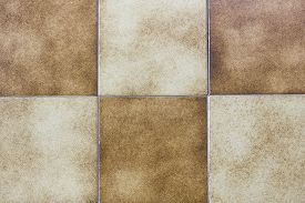 Background image of yellow and brown ceramic floor tiles.