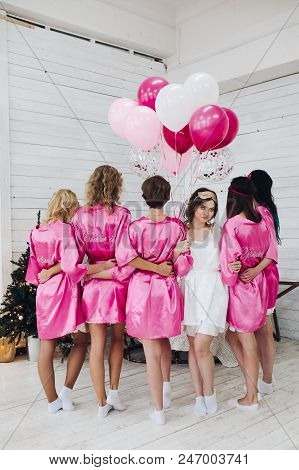 Studio Shot Of Bride-to-be In White Robe Standing With Her Bridesmaids In Pink Robe Back To Camera W