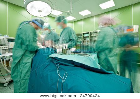 Blurred figures with medical uniforms performing surgery in operative room