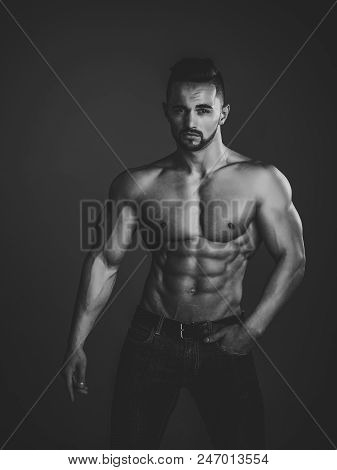 Sport And Workout. Athletic Bodybuilder Man On Black Background. Coach Sportsman With Bare Chest In