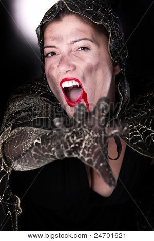 A portrait of a hooded female vampire reaching for you against black background