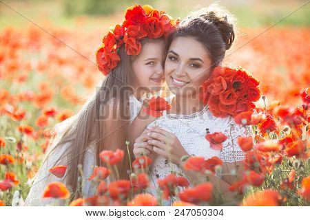 Mother And Daughter Into A Field Of Poppies.beautiful Mother And Her Daughter Playing In Spring Flow