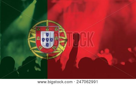 football fans supporting Portugal - crowd in stadium with raised hands against Portugese flag