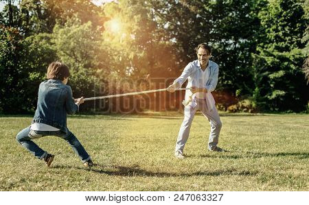 Feeling Excited. Smiling Stylish Vigorous Dad Playing Rope-pulling With His Son While The Boy Bendin