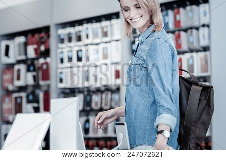 Good Gadgets. Positive Nice Smiling Woman Looking At Wonderful Modern Gadgets In A New Electronics S