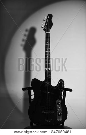 Music And Hard Rock Concept. Electric Guitar Stands On Dark Red Chair. Guitar In Deep Black Color On