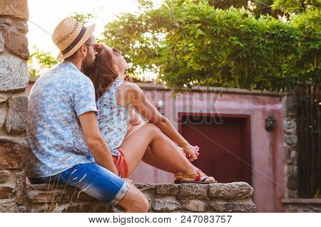 Young Couple In Love Enjoying Summer Sunset In Garden