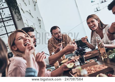 So Much Fun Together! Group Of Young People In Casual Wear Eating And Smiling While Having A Dinner