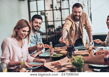 So Tasty. Group Of Young People In Casual Clothing Picking Pizza And Smiling While Having A Dinner P