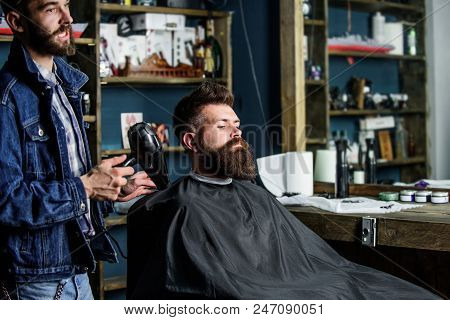 Hipster bearded client got hairstyle. Barber with hairdryer blows off hair out of cape. Barbershop concept. Barber with hairdryer works on hairstyle for bearded man, barbershop background. poster