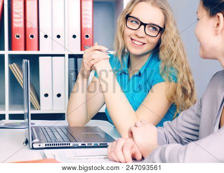 Two Young Coworkers Working Together In A Modern Coworking Studio. Business Partners Using Laptop An