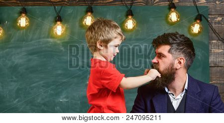 Teacher with beard, father and little son having fun in classroom, chalkboard on background. Child cheerful play with beard of teacher. Fatherhood concept. Dad with beard spend time with son. poster
