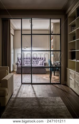 Hall In A Modern Style With Light Walls And A Glass Sliding Door. There Are Multicolored Sofas With