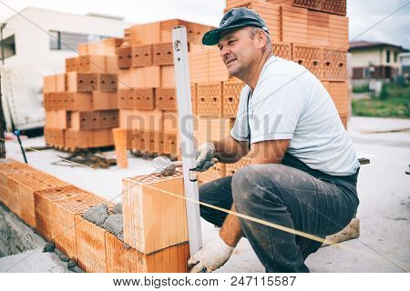 Professional Construction Worker Laying Bricks And Building House In Industrial Site. Detail Of Hand