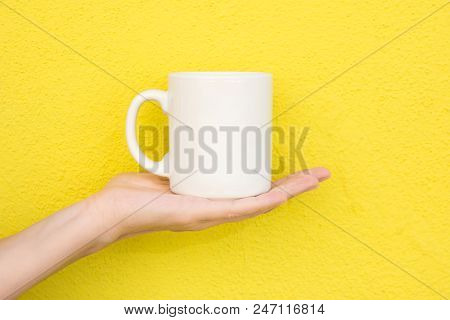 Young Caucasian Woman Holds On Hand Palm Blank Mockup White Mug On Bright Yellow Painted Wall. Airy