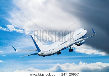 Commercial White Airplane Flying In The Blue Picturesque Sky. Travel Background Wtih Flying Airplane
