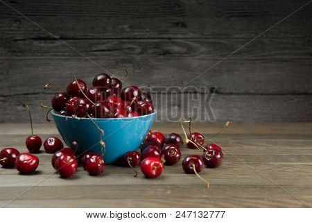 Ripe Red Cherries In Bowl On Barn Wood