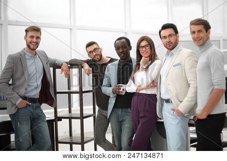group of young professionals standing in the office