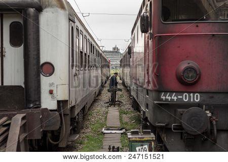 Belgrade, Serbia - May 1, 2015:  Rail Worker Manoevring Between Two Passenger Trains On The Platform