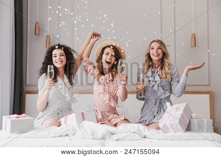 Image of pretty happy women 20s wearing dresses celebrating bridal shower in posh apartment with champagne and confetti