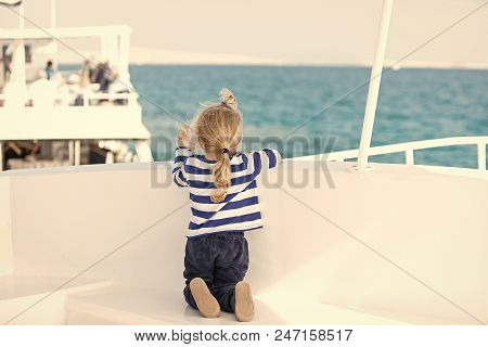 Yachting And Sailing. Small Cute Child Sitting Back On White Yacht. Childhood And Baby Care Concept.