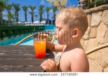 Little boy drinking juice at the pool on summer holidays