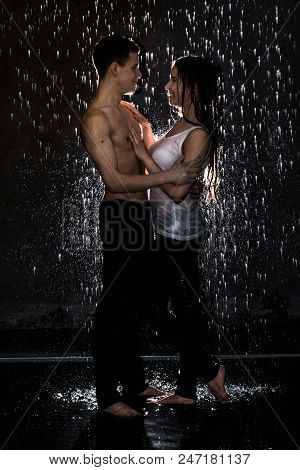 Couple Young Teens Together In The Rain And Bright Illuminated From Behind