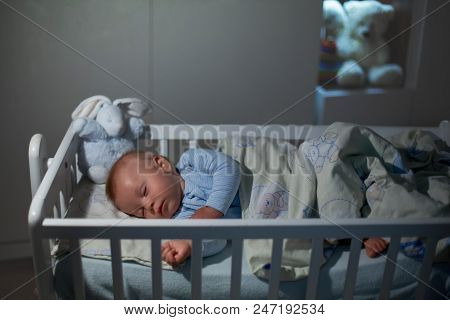 Adorable Newborn Baby Boy, Sleeping In Crib At Night. Little Boy In White Pajamas Taking A Nap In Da
