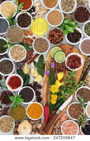 Herb and spice seasoning with fresh and dried herbs, spices and edible flowers on olive wood board and rustic background  Top view.