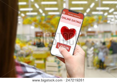 Online Dating Concept, Girl With Frameless Phone On Blurred Shop Background