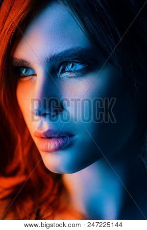 Close-up portrait of a beautiful young woman with red hair and expressive eyes. Beauty, cosmetics, makeup. Hair styling.
